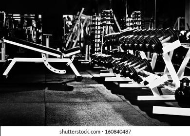 many black dumbbells in dark weight room, horizontal photo