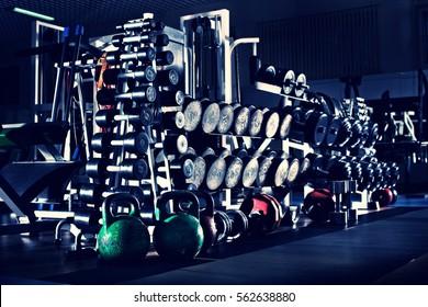 many black dumbbells in gym room, horizontal photo, blue; violet tone
