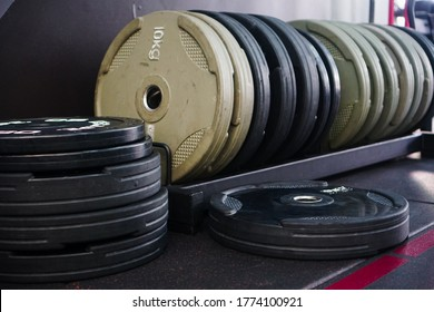 Many black weight plates of 25 kg were placed in the gym. And many other weight plates are placed in the bin for use in lifting and exercise.
