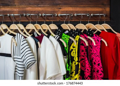Many blouses on hangers in the dressing room.