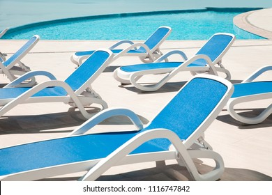 Many blue chaise lounge by the pool. Resort spa concept.