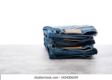 many blue jeans. men fashion denim jeans stacked over white background.