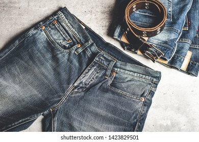 many blue jeans on concrete background. men fashion denim jeans.