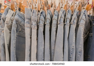 many blue jeans on the rack in shop for sale.