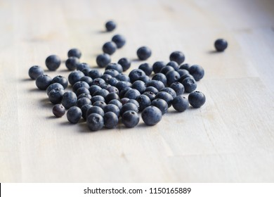 Many blueberries on wooden background