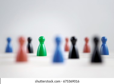 Many board game pawns on table, selective focus on the green one. Being brave, be yourself and originality concept. Diversity and tolerance.