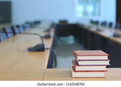 Many books are stacked on a table in a conference room selective focus and shallow depth of field