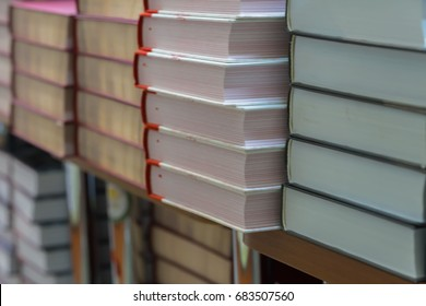 Many books, textbooks or fiction in rows lying on shelves in library or in modern urban bookshop. Self-study, educational, manuals, textbooks, school, study concept. Blurred abstract background