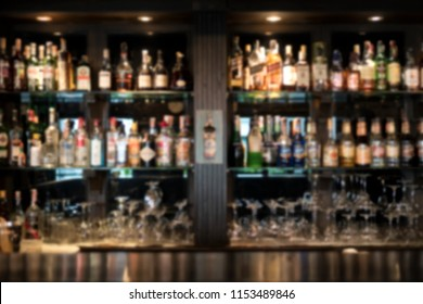Many bottles of liqueurs on bar shelves and bar counter in front of