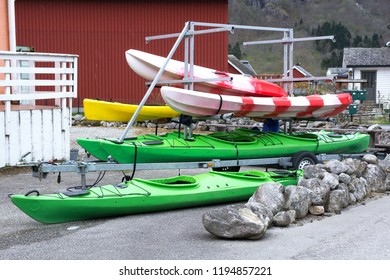 Many bright colored recreational canoe and kayak. are located on storage rack  in anticipation of good weather