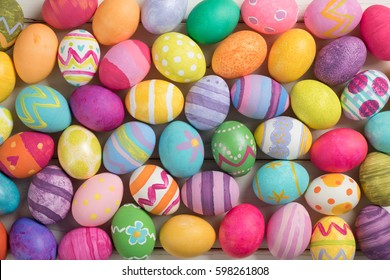 Many Bright and Colorful Easter Eggs Filling the Background.  They are hand-painted or dyed.  It's a closeup, or macro, with a horizontal top view in flat lay style that can be used vertical.