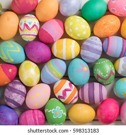 Many Bright and Colorful Easter Eggs Filling the Background.  They are hand-painted or dyed.  It's a pretty closeup, or macro, with a square top view crop in flat lay style.
