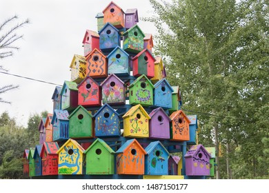 Many bright colorful wooden birdhouses (nesting boxes) located close to each other, painted by little kids