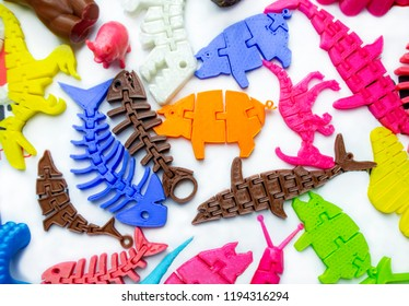 Many bright multi-colored objects printed on 3d printer lie on flat surface close-up. Fused deposition modeling, FDM. Concept modern progressive additive technology for 3d printing.