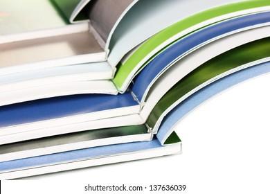 Many bright open magazines close-up