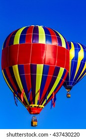 Many brightly colored hot air balloons aloft in early morning blue sky