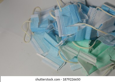 many broken unused disposable mask with blue, white and green colors