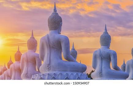 Many Buddha statue on sunset