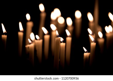 Many burning candles - Light of candels in the church on the black background