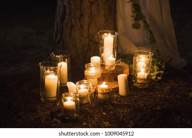 Many burning candles on ground. Beautiful place for outside wedding ceremony in wood.