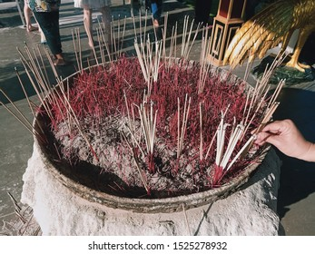 Many burning joss sticks and incense for worship Buddhism and Asian cultural belief which stand on fully ash censer with background of blurry smog and people in Temple.