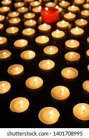 Many burning tea light candles, one candle in form of heart