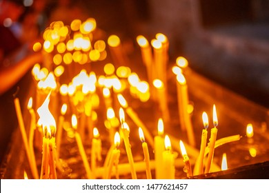 many burning wax candles in Church are lit by believers during prayer to God, a bright warm flame as a symbol of faith in front of altar, icons in interior of ancient monastery, religious ritual