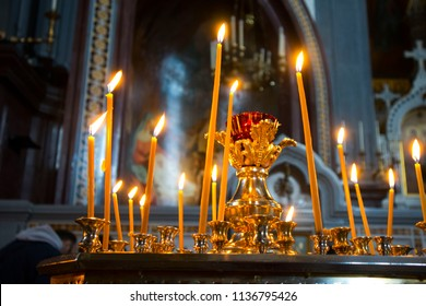 Many burning wax candles in the orthodox church or temple