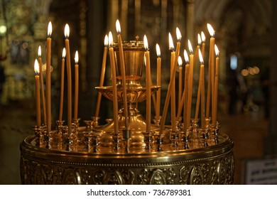 Many burning wax candles in the orthodox church