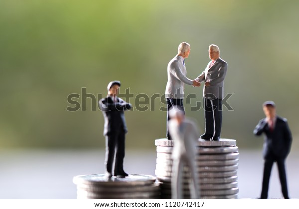 Many Business man,saving,investment and finance concepts. Miniature people Stand  on a rows coin,soft focus and blurred style.