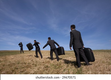 many businessmans in the field walking with his luggage