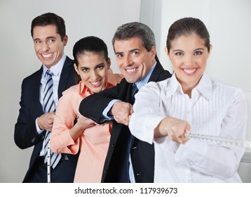 Many businesspeople acting in concert while pulling on a string