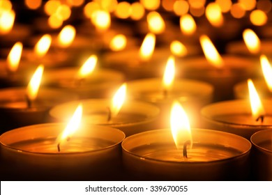 Many candle flames glowing in the dark, create a spiritual atmosphere
