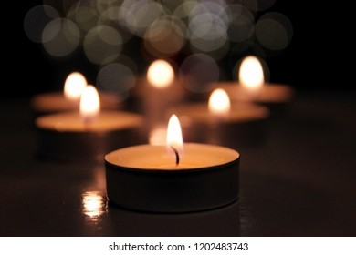 Many candle flames glowing on dark background. Close-up. Free space.