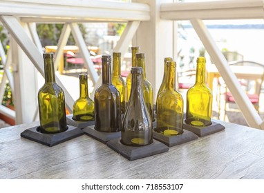 Many candle holders made from wine bottles on wooden table