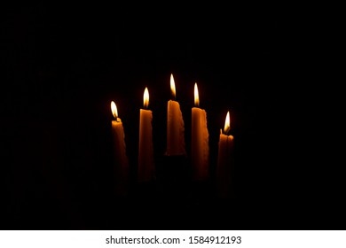 Many candles in a dark room, five white and tall standing candles with a flame. Candle flame. A lit and burning candle. Selective focus.