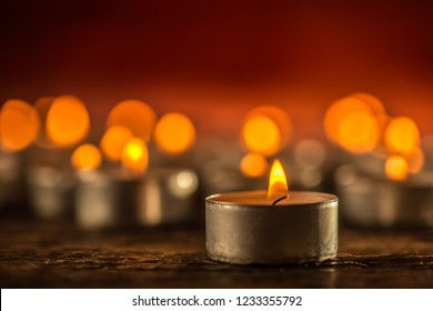 Many candles symolizing funeral religios christmas spa celebration birthday spirituality peace memorial or holiday burning at night.