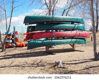 Many canoes being stored in a rack during off-season