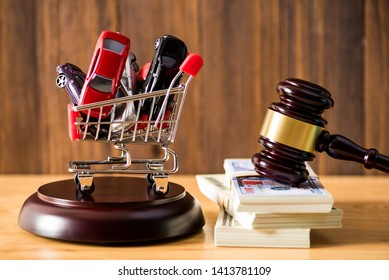 many car model figure in shopping cart and auction hammer over money bank note