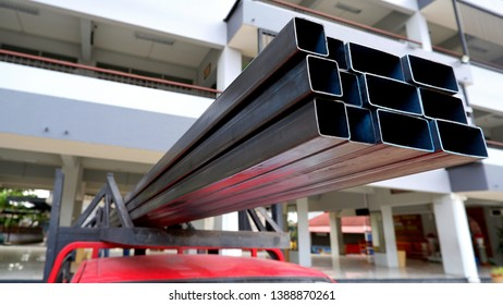 Many carbon steel rectangular tubes on top of red pick up car with blurred background in convenient very longer materials transmission in transport concept, selective focus with blurred background