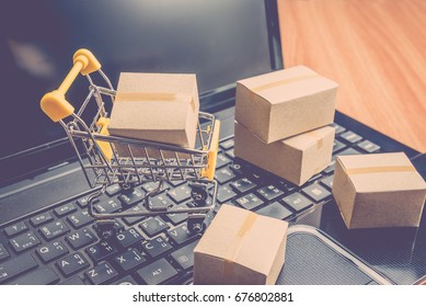 Many cardboard boxes or carton and trolley on laptop. Online shopping e-commerce and logistic shipping freight transportation. Online business concept.