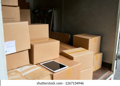 Many cardboard boxes and digital tablet insite delivery truck