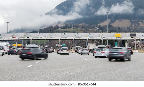 Many cars approaching toll gate on highway, mountain scenery