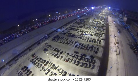 Many cars on big parking at dark snowy winter night. Aerial view