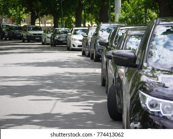 Many cars parked and lined up in a curve urban street. Melbourne, VIC Australia.