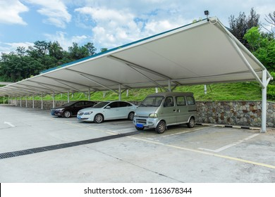 Many cars are parked in open-air parking lots with steel awnings on the vehicles, in the city in sunny summer