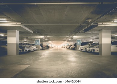 Many cars in parking garage interior, industrial building. Vintage filter effect.