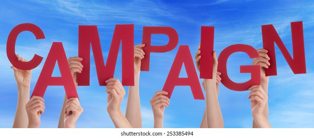 Many Caucasian People And Hands Holding Red Letters Or Characters Building The English Word Campaign On Blue Sky