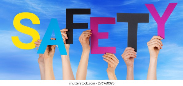 Many Caucasian People And Hands Holding Colorful  Letters Or Characters Building The English Word Safety On Blue Sky