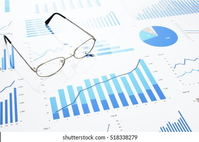 Many charts and glasses. Reviewing data. Financial reports and glasses. Reflection background.